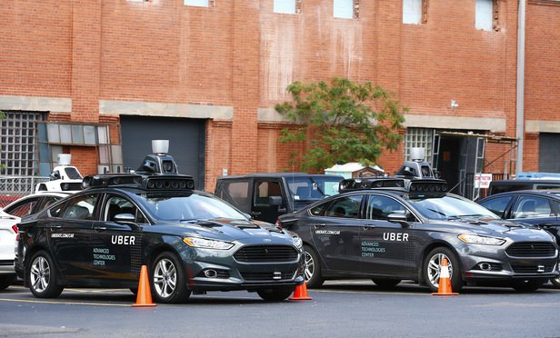 Self-driving Ford Fusion hybrid cars sit parked, Thursday, Aug. 18, 2016, in Pittsburgh. Uber said that passengers in Pittsburgh will be able to summon rides in self-driving cars with the touch of a smartphone button in the next several weeks. (Photo: Jared Wickerham/AP)