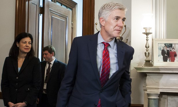 Supreme Court nominee Judge Neil Gorsuch, right, walks down the hallway inside the Russell Senate Office Building to meet with Senator Jeff Flake (R-AZ) on Wednesday, February 8.