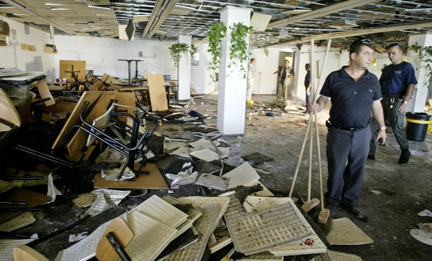 Workers clean the inside of a cafeteria hours after a bomb exploded at Hebrew University in Jerusalem, killing nine, four of them Americans, and wounding more than 70, on July 31, 2002.(Photo: David Guttenfelder/AP)