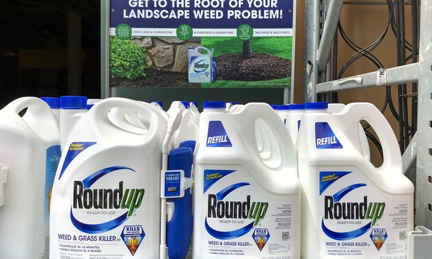 Garden supply store shelf with containers of Round up weed control.