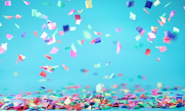 Colored confetti flying on blue background.