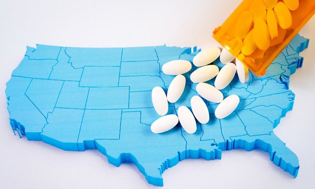 U.S. map with opioid pill bottle pouring over it