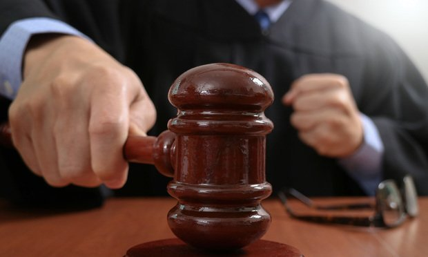 Male judge in a courtroom striking the gavel,