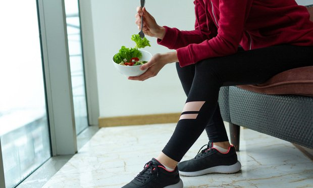Fitness woman in sneakers is resting and eating a healthy, fresh salad after a workout. Fitness and healthy lifestyle concept.