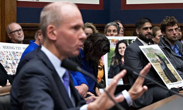 Family members of Boeing Co. 737 Max crash victims hold photographs as Dennis Muilenburg, chief executive officer of Boeing Co., second left, speaks during a House Transportation and Infrastructure Committee hearing in Washington, D.C., U.S., on Wednesday, Oct. 30, 2019. Muilenburg yesterday declined to endorse specific reforms to bolster safety oversight of the aerospace giant during a sometimes angry grilling in his first appearance before Congress since two 737 Max crashes killed 346 people. Photographer: Andrew Harrer/Bloomberg