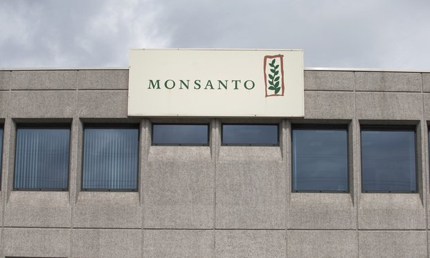 The Monsanto Co. logo sits on a sign outside the Roundup herbicide manufacturing facility in Antwerp, Belgium, on Tuesday, June 14, 2016. The next step in Bayer AG's quest to buy Monsanto and create the world's largest agricultural company is likely to hinge on whether the U.S. seed giant will agree to open its books. Photographer: Jasper Juinen/Bloomberg