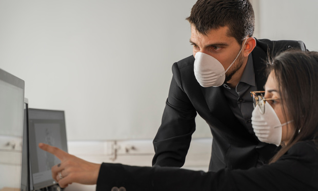Coronavirus office workers with mask for corona virus. Business workers wear masks to protect and take care of their health. Office working with computer. Working from home. Photo: Deliris/Shutterstock