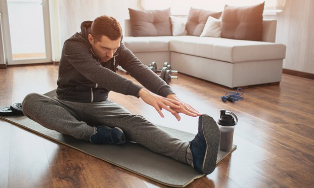 oung ordinary man go in for sport at home. Freshman or beginner stretching with tow hands to one leg. Excercising alone in empty apartment. Try to keep fit and stay healthy with good body.