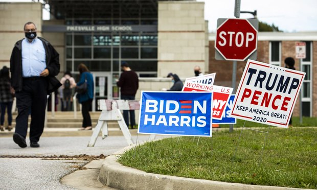 Biden Harris and Trump Pence campaign signs outside the entrance to Pikesville High School as people stand in line to cast their vote in the 2020 Presidential Election in Baltimore, MD, on November 3, 2020. Photo: Diego M. Radzinschi/ALM