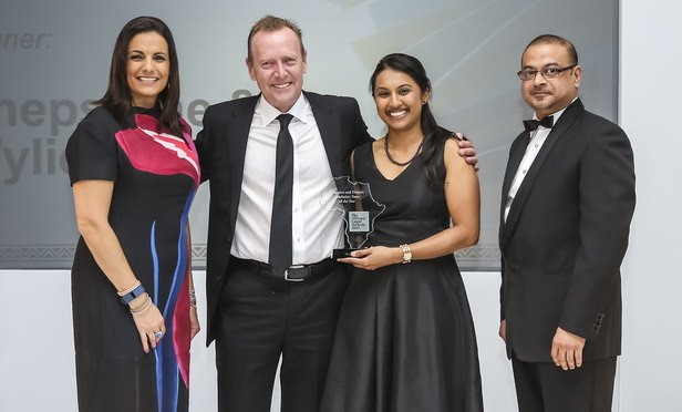 Bruce Armstrong, partner, and Nerisha Besesar, senior associate, collect their award from host, Broadcaster Leanne Manas (left) and awards judge Pavel Hassim, FirstRand Bank