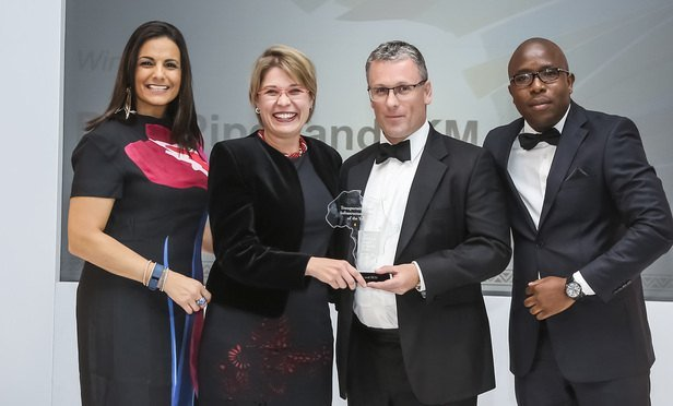 Liza Odendaal, business development manager, and Colin Wilson, partner, collect their award from host, broadcaster Leanne Manas (left), and awards judge Talenta Chavalala, senior legal adviser, Development Bank of Southern Africa