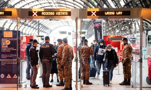 Members of the military and police check commuters' travel authorization forms at Centralerailway station in Milan, Italy, on Tuesday, March 10, 2020. Italy has become the first country to attempt a nationwide lockdown to stop the spread of the highly infectious coronavirus.
