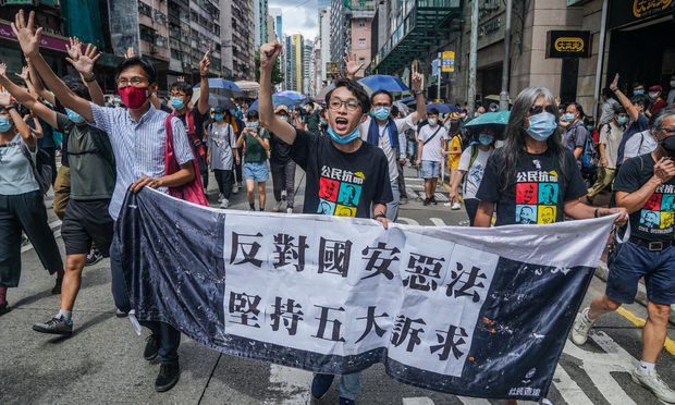 Pro-democracy demonstrators carry a banner against the new national security law as they march during a protest in Hong Kong, on Wednesday, July 1, 2020.