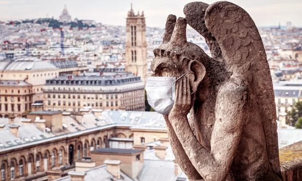 Gargoyle on Notre Dame overlooking Paris wearing a face mask.