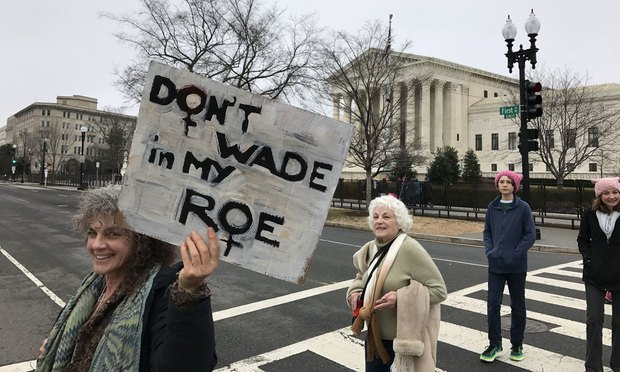 Protesters stream by the U.S. Supreme Court on Jan. 21, 2017, as part of a women's march on Washington.