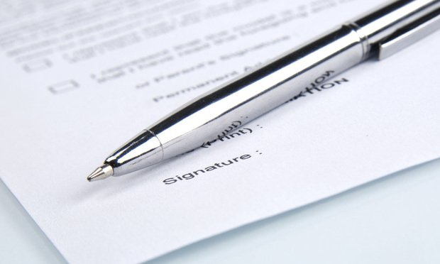 paper contract with a pen and a signature line