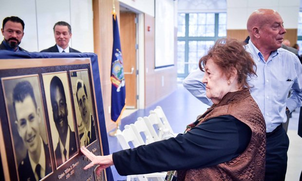 Rita Wallace, mother of Sgt. Michael Wallace, touches his photo after the unveiling of a plaque at the brand new Court Officers Academy in Brooklyn. ..The training facility is named after New York State Court Officers Capt. William Thompson, Sgt. Thomas Jurgens and Sgt. Michael Wallace who died on 9.11.01...(Photo by David Handschuh/NYLJ)