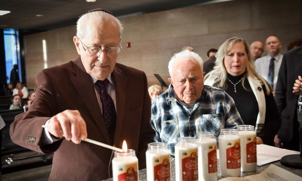 Holocaust survivors Irving Roth and Isadore Katz, joined by Katz's daughter Renee Katz-Packer, light candles during the Brandeis Association's 12th annual Holocaust remembrance program at the Queens County Civil Court Jury Room