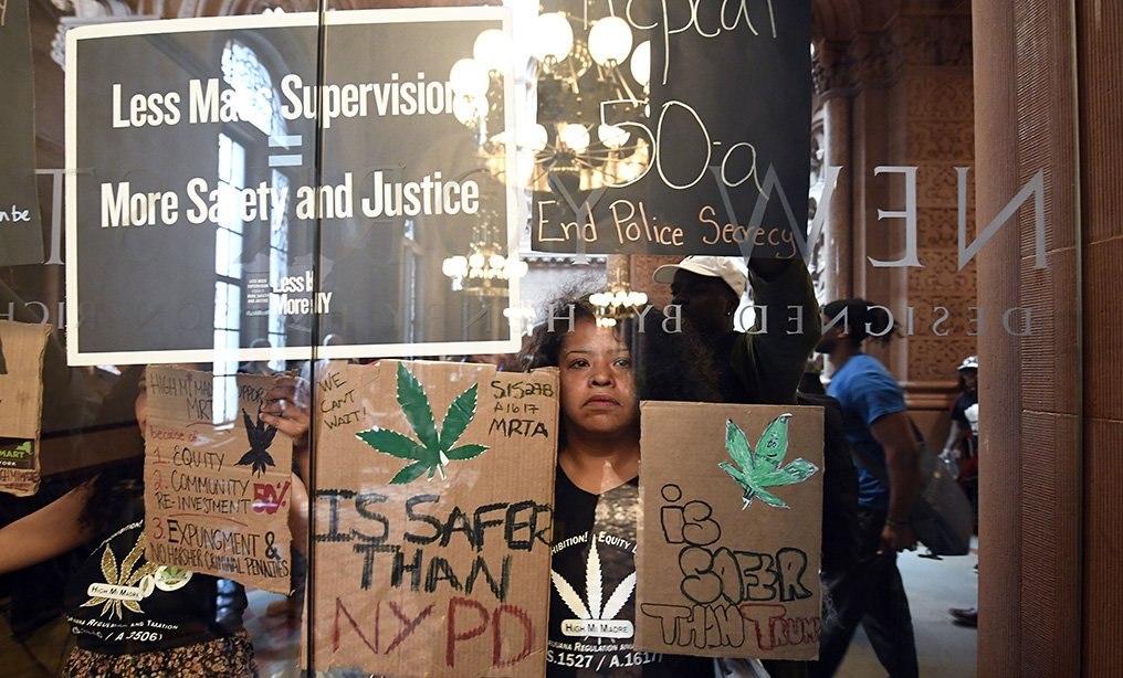 Pilar DeJesus with a coalition of protesters urging legislators to pass Marijuana legislation holds a sign against the senate lobby doors at the state Capitol in Albany on Wednesday.