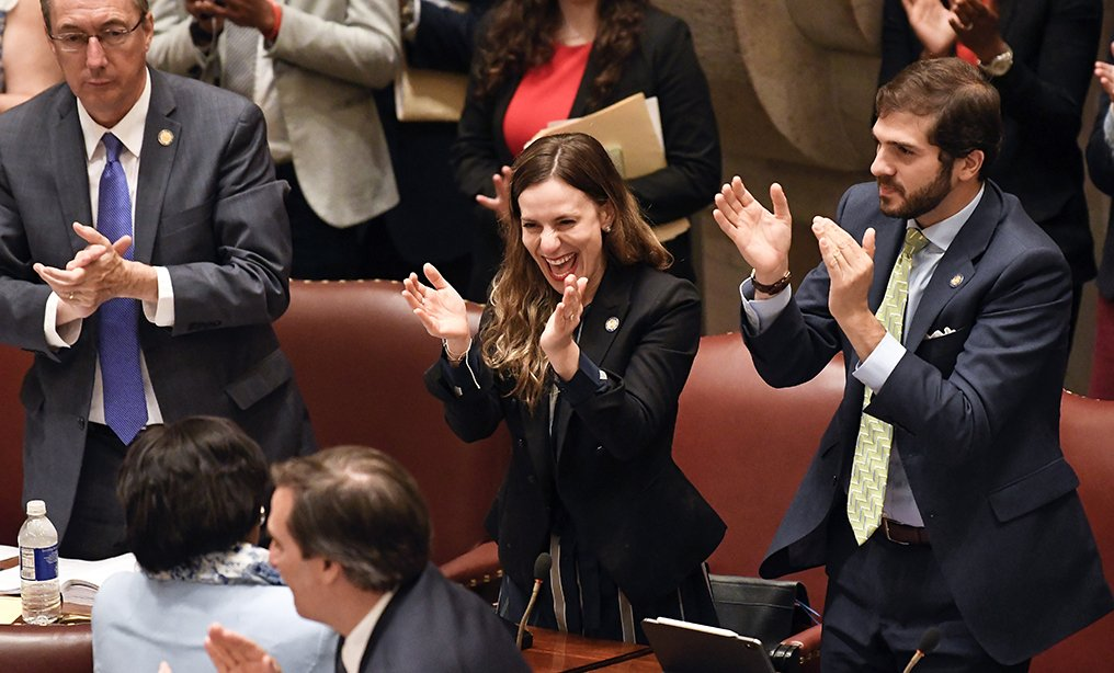 New York Sen. Alessandra Biaggi, D-Bronx, center, celebrates after her legislation passed to change state legal standards on sexual harassment at the state Capitol in Albany on Wednesday.