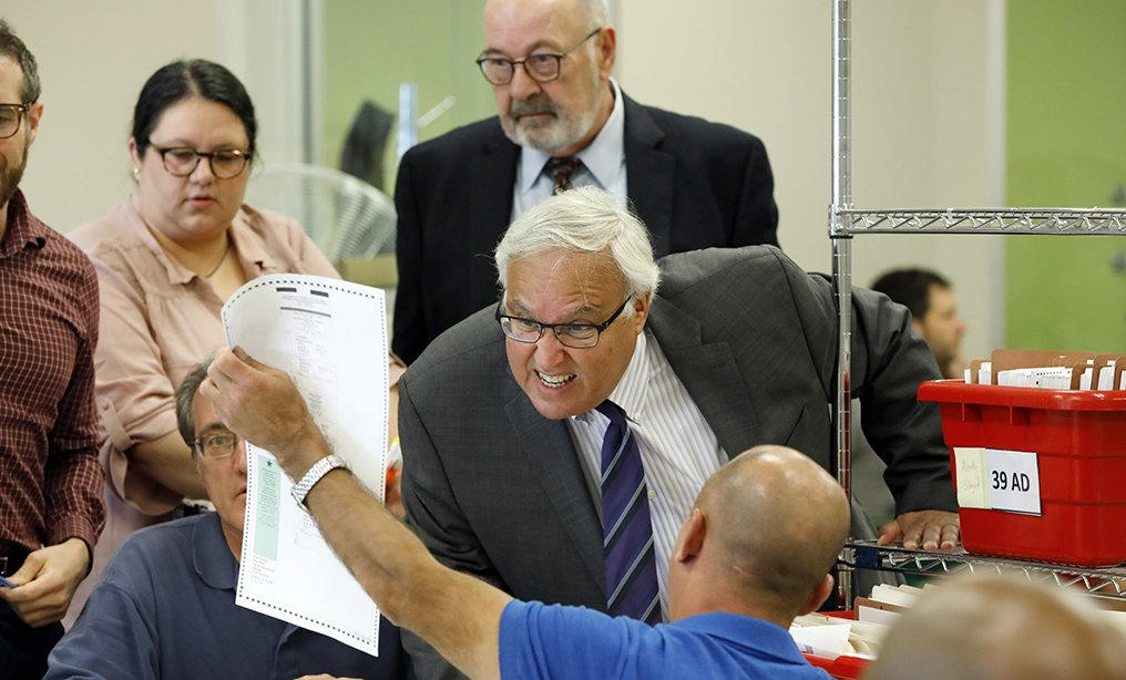 Attorneys for Queens Borough President Melinda Katz, Marty Connor, foreground right, and Michael Reich, background right, examine a ballot during the vote recount in the primary election for Queens County District Attorney between Katz and public defender Tiffany Cabán, Queens last week.