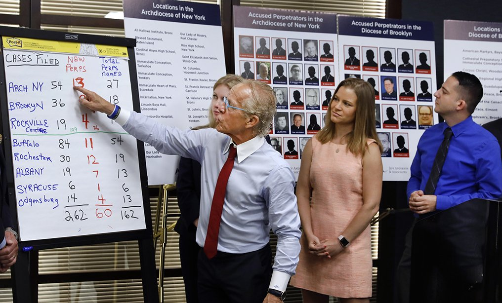 Attorney Jeff Anderson, left, points to a chart of sexual abuse perpetrators as sexual abuse victims Birdie Farrell, center, and Joseph Caramanno watch during a news conference in New York on Aug. 14. Wednesday marked the start of a one-year litigation window in New York allowing people to file civil lawsuits that had previously been barred by the state's statute of limitations, which was one of the nation's most restrictive before lawmakers relaxed it this year.