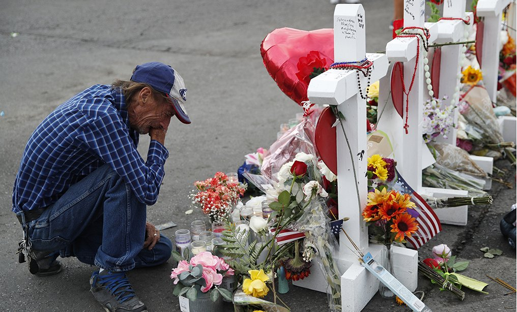 Antonio Basco cries beside a cross at a makeshift memorial near the scene of a mass shooting at a shopping complex in El Paso, Texas earlier this month. Basco's wife was among 22 people fatally shot on Aug. 3 at a the local Walmart.