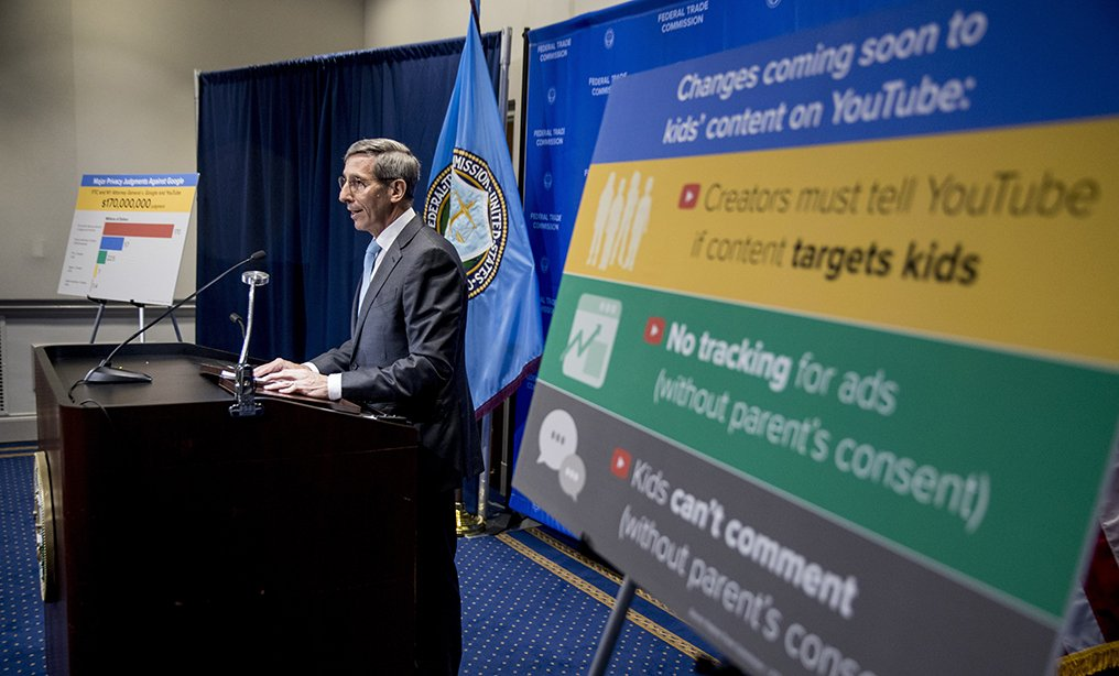 A sign with coming changes to kids' comment on YouTube is displayed as Federal Trade Commission Chairman Joe Simons speaks at a news conference at the Federal Trade Commission in Washington, Wednesday, Sept. 4, 2019, to announce that Google's video site YouTube has been fined $170 million to settle allegations it collected children's personal data without their parents' consent. (AP Photo/Andrew Harnik)