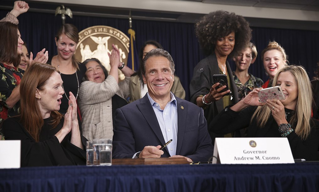 Surrounded by supporters and activists, Gov. Andrew Cuomo signs a bill that increases the statute of limitations in rape cases during a bill signing ceremony on Wednesday, Sept. 18. Actresses Julianne Moore, left, and Mira Sorvino, right, were there as supporters of the bill and members of the Time's Up movement, which advocates for women's rights. Photo: Seth Wenig/AP
