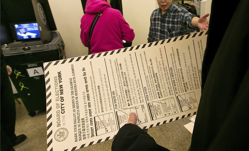 A voter carries her ballot to be scanned at a polling place in New York. Photo: Richard Drew/AP