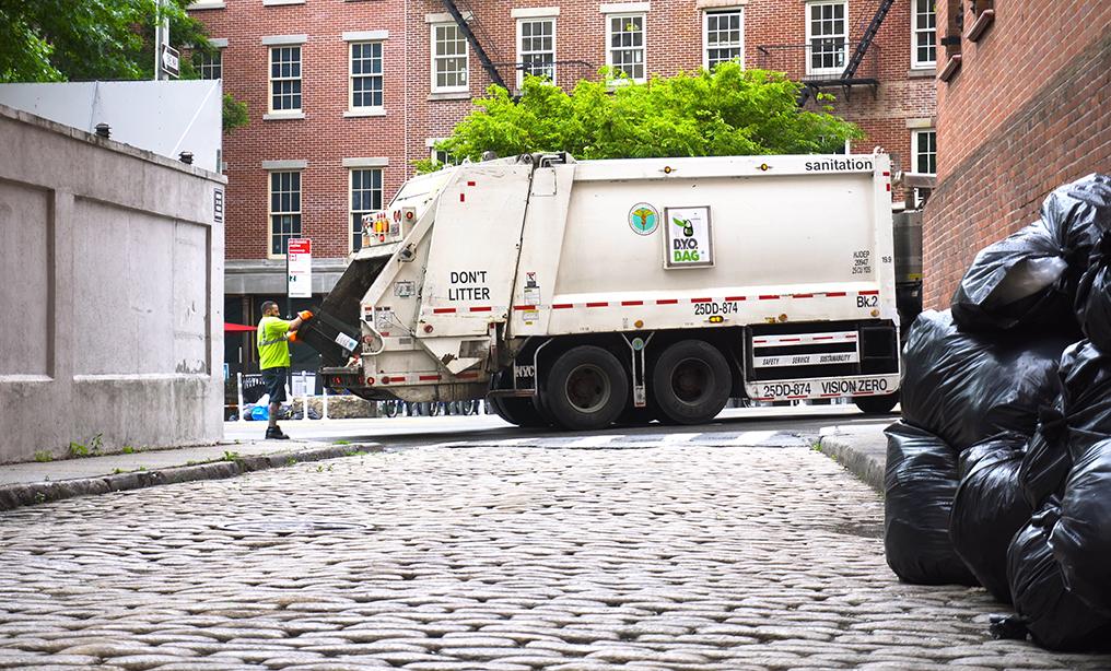 New York Department of Sanitation truck collects trash alongside city street. Photo: BrandonKleinVideo via Shutterstock