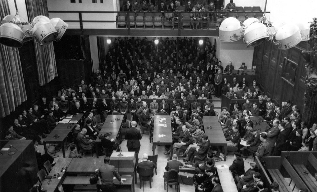 An aerial shot of the courtroom showing Pastor Gerecke speaking at the Thanksgiving Day service in Nuremberg in 1945. Justice Jackson's head is bowed respectfully—perhaps in keeping with his assignment from President Truman and U.S. representational role, his general irreligiousity notwithstanding. And throughout the courtroom, many other heads are bowed too. Courtesy photo