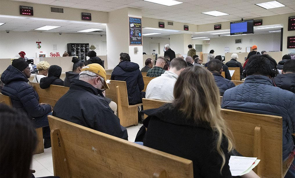 People wait to be served in a Department of Motor Vehicles office, Monday, Dec. 16 in New York. Photo/Mark Lennihan/AP