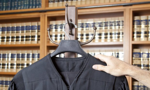 Hand and judicial robe photo illustration. (Photo: Jason Doiy and S. Todd Rogers/ALM)