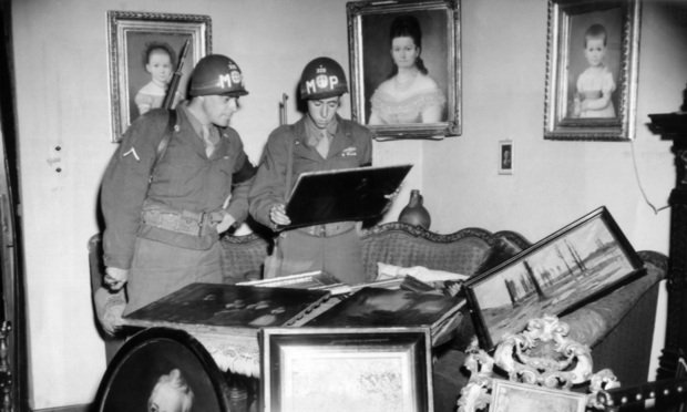 Military policemen Pfc. Matt Carlson (left), Detroit, Mich., and Pfc. Sy Herold (right), New York, N.Y., look over one of Lady Astor's Van Dyke paintings Remagen, Germany on July 7, 1945, value at $50,000, which was part of the loot discovered in the home of Dr. Rudolph Reppert, local Nazi leader. (AP Photo/Peter J. Carroll)