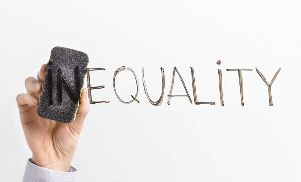 Equality concept. Man cleaning part In in word Inequality written on glass board, copy space By Prostock-studio/Shutterstock