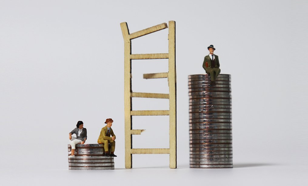 Miniature wood broken ladder and miniature people sitting on the pile of coins. The concept of economic inequality. By Hyejin Kang/Shutterstock