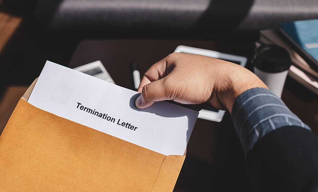 Termination of Employment and layoff concept, Businessman holding Termination of Employment Form in paper brown envelope. By Chayantorn Tongmorn/Shutterstock