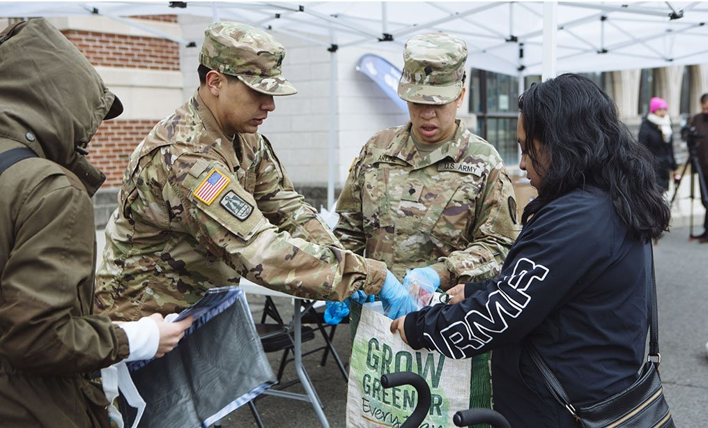 Members of the New York Army National Guard hand out bags of food to residents at a food distribution station outside a high school in New Rochelle, N.Y., on Thursday, March 12. Members of the National Guard have arrived in New Rochelle to clean institutions and deliver food to the more than 120 sick residents within the three mile containment area – state's first coronavirus containment zone. Photo: Angus Mordant/Bloomberg