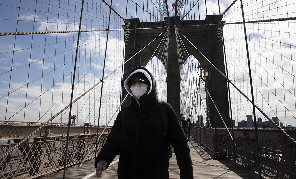 A woman wears a mask as she crosses the Brooklyn Bridge on Monday, March 16 in New York. Photo: Mark Lennihan/AP