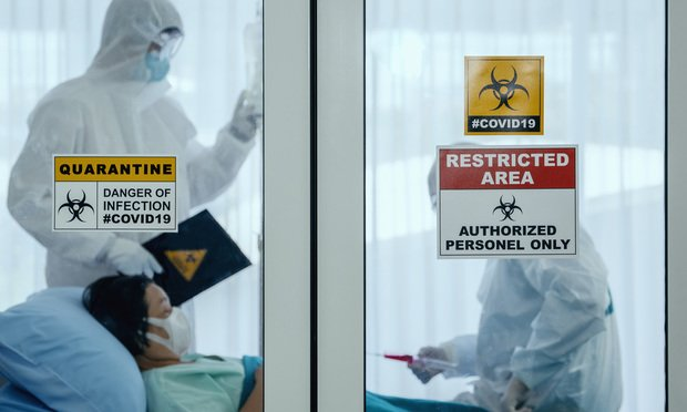 <i>Two medical staff wearing protective suits treating a woman infected with coronavirus(Covid-19) inside an isolation ward at a hospital. Photo: Mongkolchon Akesin/Shutterstock.com</i>