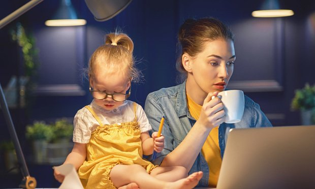 Young mother with toddler child working on the computer from home at night..