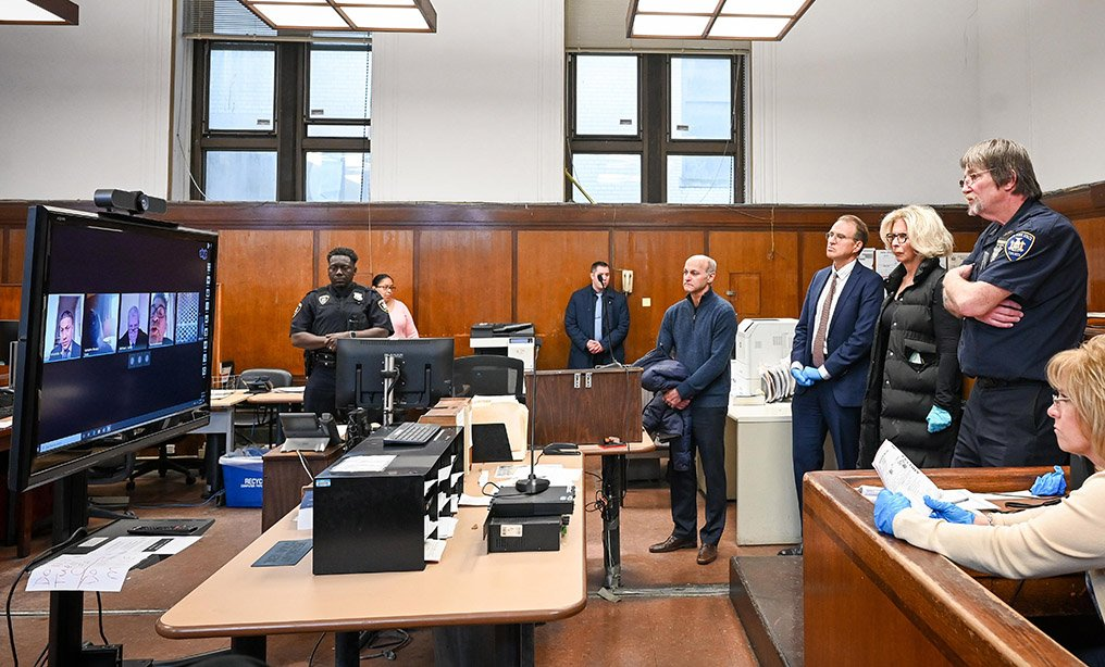 Chief Judge Janet DiFiore, foreground third from right, and Chief Administrative Judge Lawrence K. Marks, foreground, second left, observe a virtual arraignment at Criminal Court in New York last month. State courts are moving to virtual court operations. New York Unified Court System via AP