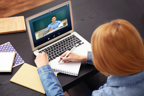 Woman video conferencing on laptop at home
