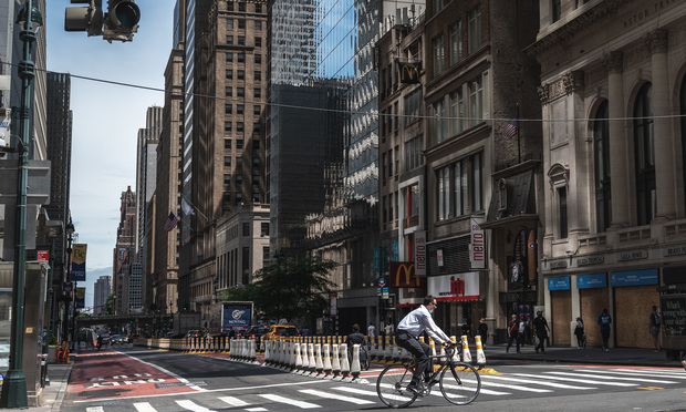 A man rides his bike through Midtown Manhattan, New York. Photo: Ryland West/ALM
