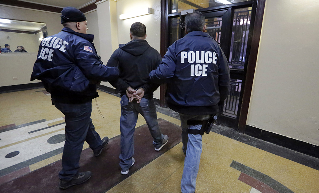 Immigration and Customs Enforcement officers escort an arrestee in an apartment building in the Bronx. Photo: Richard Drew/AP