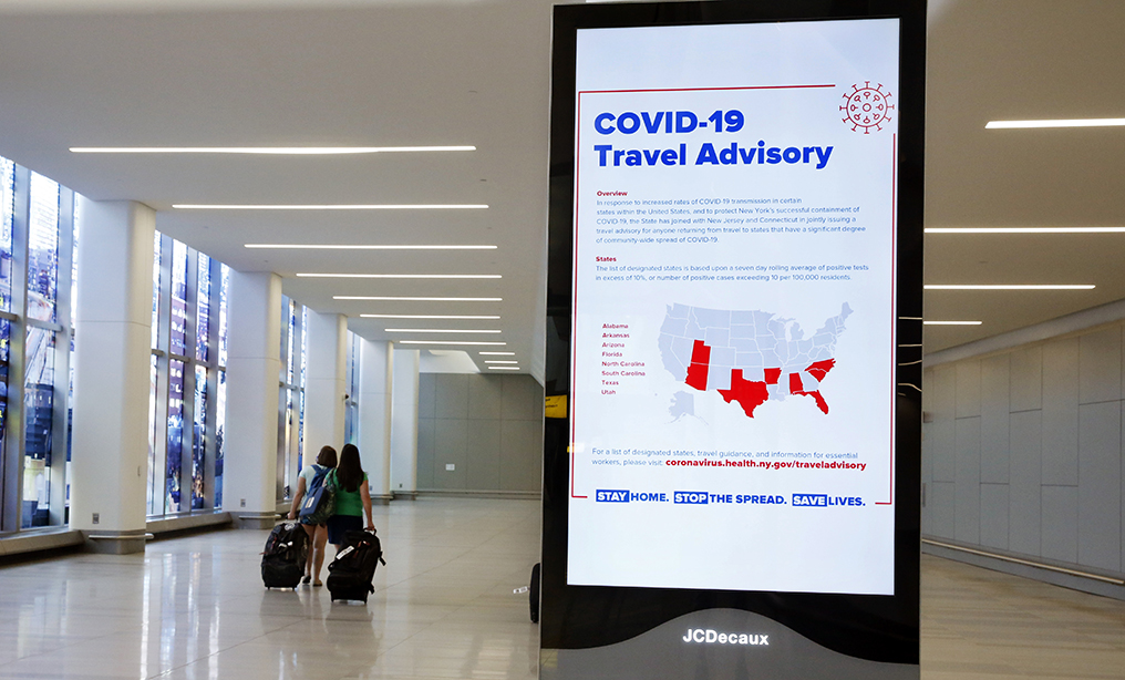 A sign outside the baggage claim area of Terminal B at LaGuardia Airport alerts passengers from states with high COVID-19 cases to quarantine themselves for 14 days. Photo: Kathy Willens/AP