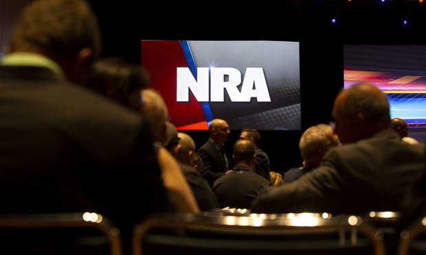 A National Rifle Association logo is displayed above members during an NRA annual meeting. Photographer: Daniel Acker/Bloomberg