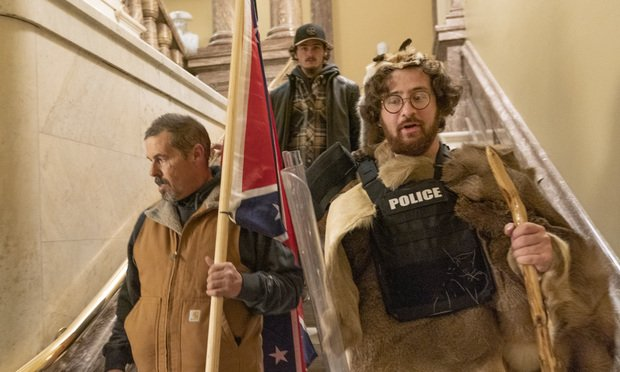 Aaron Mostofsky, son of New York Supreme Court Judge Shlomo Mostofsky, is seen on the right wearing a fur coat and police vest walking down the stairs outside the Senate Chamber as violence erupts at the Capitol after demonstrators breached the security and stormed the U.S. Capito Jan. 6, 2021. in Washington, D.C. Photo: Manuel Balce Ceneta/AP