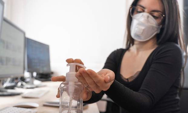 Woman cleaning her hands at the office. Workplace desk with computer. Woman spraying alcohol gel or antibacterial soap sanitizer. Photo: Deliris/Shutterstock
